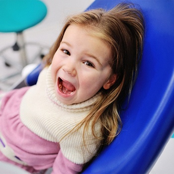 A little girl sitting in the dentist's chair with her mouth open in preparation for fluoride treatments