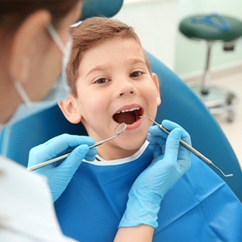 A little boy having his teeth examined to determine where the tooth-colored filling should be placed