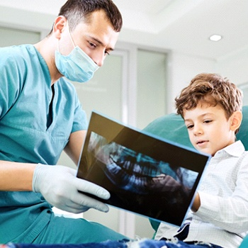 A dentist showing a young boy his dental X-Rays during an appointment