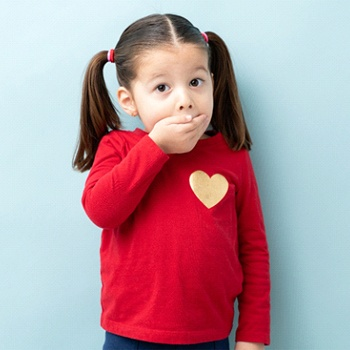 A little girl with pigtails covering her mouth with her hand