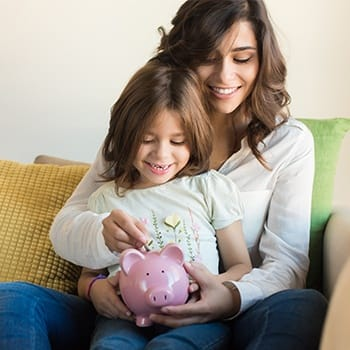 Mother and daughter placing change in a piggy bank