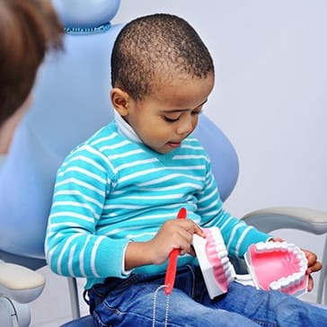 child learning about how to brush their teeth with their children's dentist in Duncanville