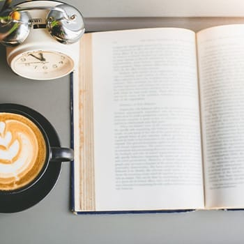 Coffee and an open book on a table