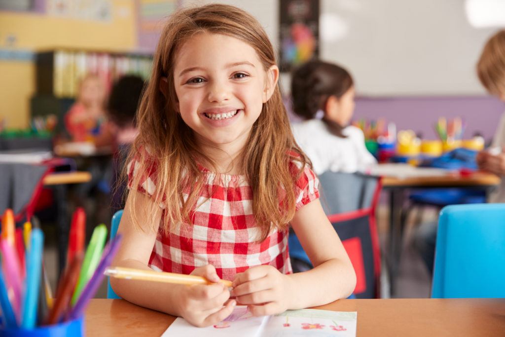 Child smiling while completing work in classroom